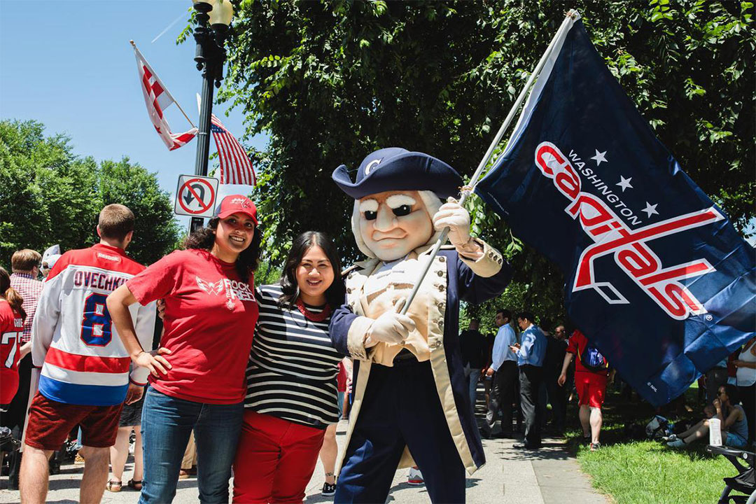 George mascot with two students at the Capitals Stanley Cup Parade