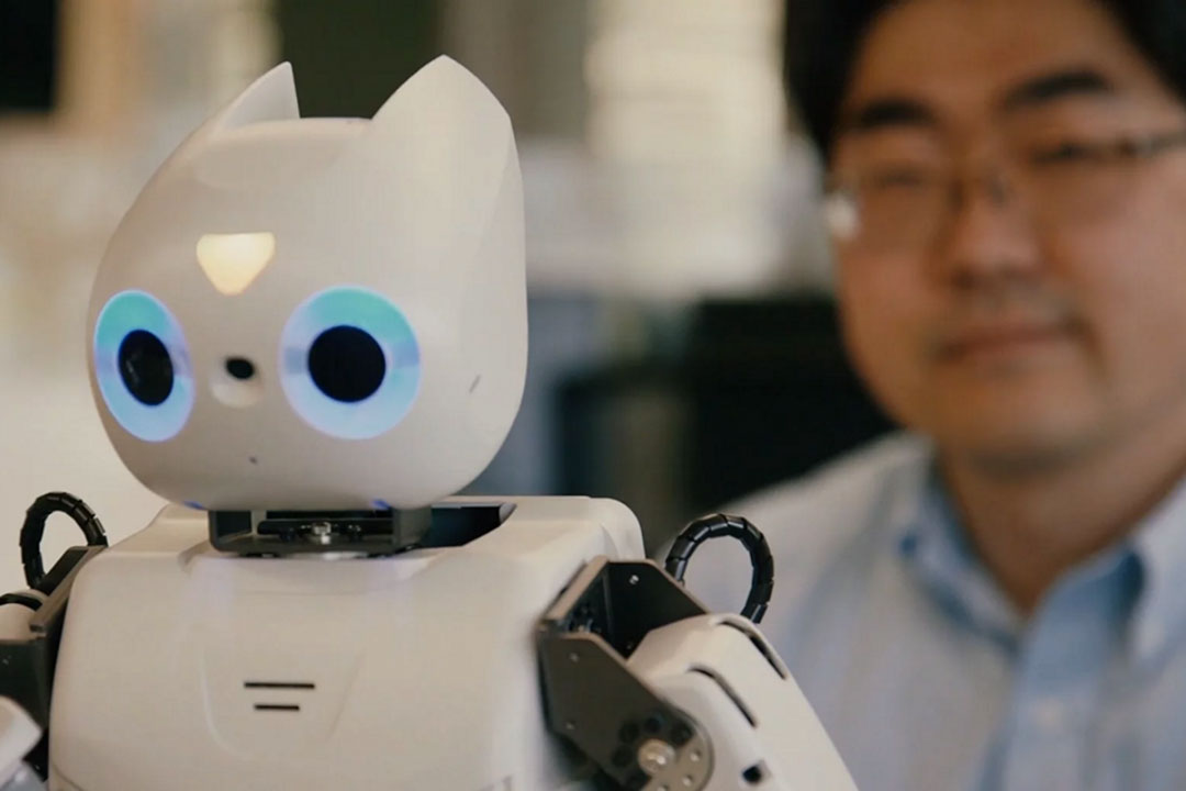 Professor looking at robot he uses to help children with autism